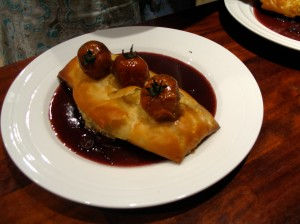 Leek & Mushroom Strudel with roast tomatoes on white plate