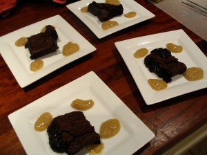 Chocolate brownies with raspberry coulis served on white plates