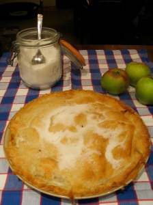 Apple tart with cooking apples and jar of caster sugar in background