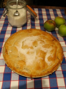 Apple tart on blue and white t-towel with jar of sugar and apples in background.