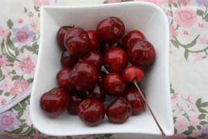 White bowl of cherries on pink apron