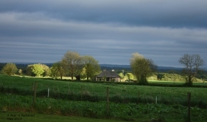 Dark thundery clouds and bright sunshine behind cottage